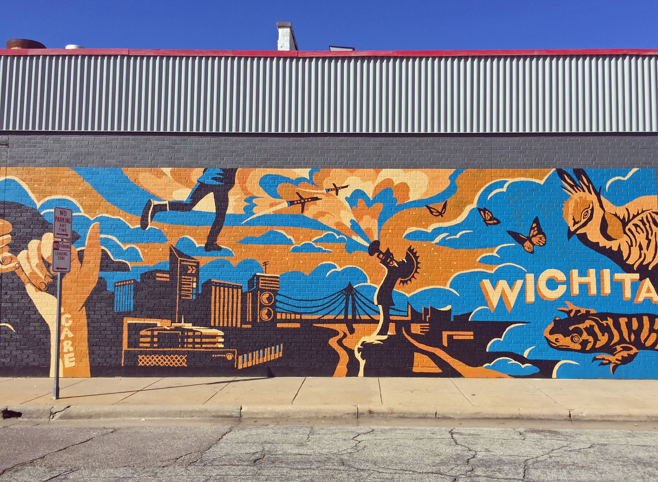 "A bold blue and yellow mural that says ""Wichita"" on a side street in the city."